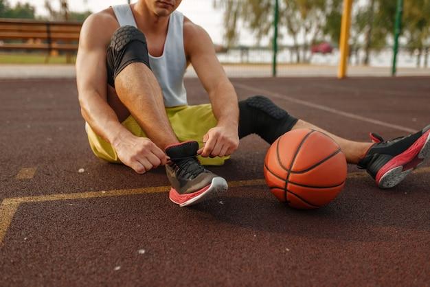 Basketballspieler, der auf dem boden sitzt und schnürsenkel auf dem außenplatz bindet.