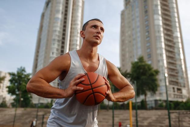 Basketballspieler, der den wurf auf dem außenplatz anstrebt.