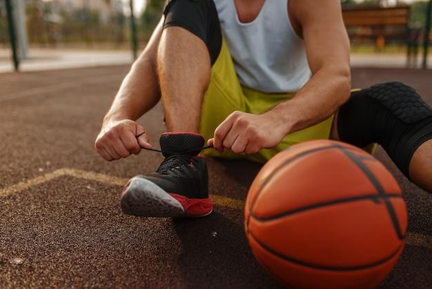 Basketballspieler, der schnürsenkel auf dem außenplatz bindet