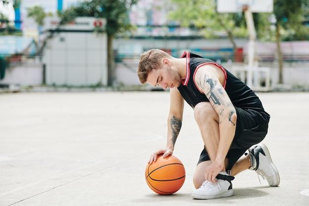 Basketballspieler, der schuhe bindet