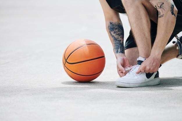 Basketballspieler, der sportschuh bindet