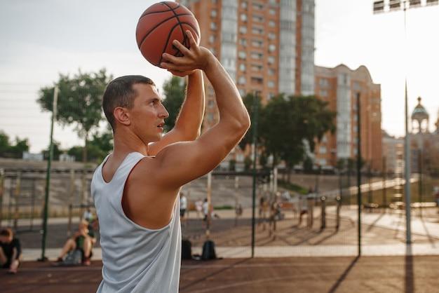 Basketballspieler macht einen wurf auf dem außenplatz.