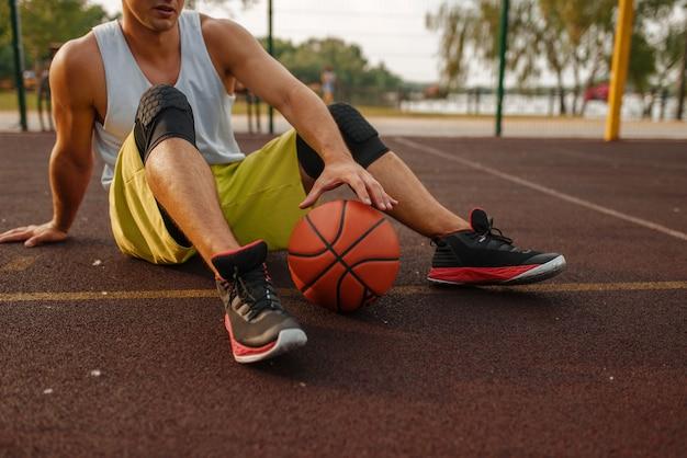 Basketballspieler mit ball, der auf dem boden auf dem außenplatz sitzt.