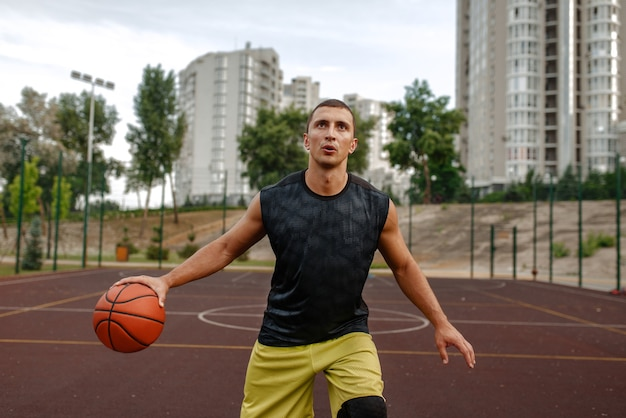 Basketballspieler mit ball in bewegung auf dem außenplatz.