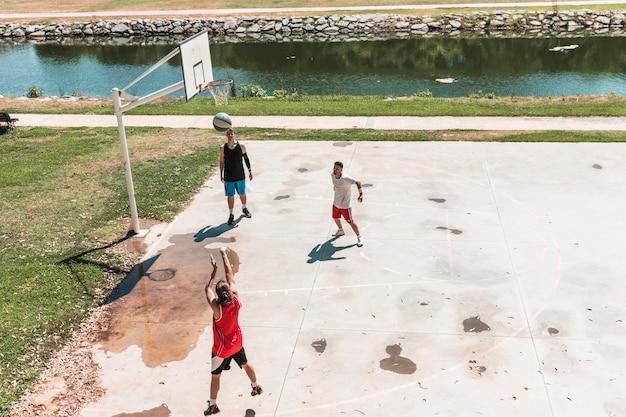 Basketballspieler mit drei spielern, der draußen gericht spielt