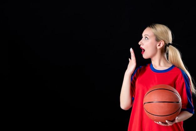 Basketballspielerin mit ball auf einem dunklen, isolierten hintergrund athlet spielen spielaktion