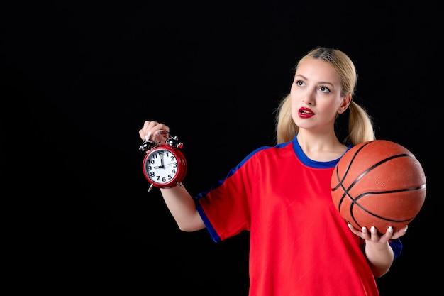 Basketballspielerin mit ball und uhren auf schwarzer oberfläche athlet game action play