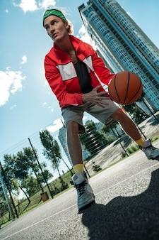 Basketballtraining. netter profispieler, der einen ball hält, während er trainiert, um basketball zu spielen