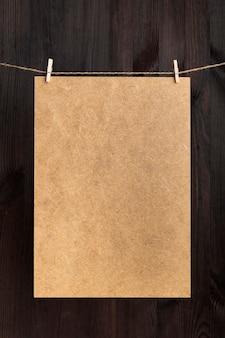 Bastelkarton mit wäscheklammern am seil hängend. platz für ihren text. kopieren sie platz, modell. vertikaler rahmen
