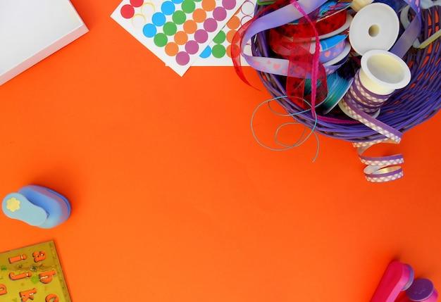 Basteln mit bunten bändern, schlägen und aufklebern auf einem orangefarbenen hintergrund