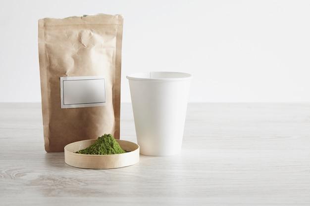 Basteln sie eine braune papiertüte, nehmen sie glas und premium-bio-matcha-teepulver in der schachtel auf weißem holztisch weg, der auf einfachem hintergrund lokalisiert wird. bereit für die vorbereitung, verkaufspräsentation.