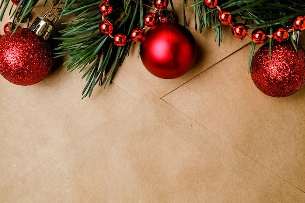 Basteln sie einen umschlag mit einem zweig vom weihnachtsbaum, roten kugeln und einer girlande