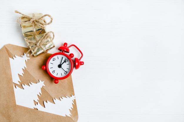 Basteln sie einen umschlag mit weihnachtsbäumen, einem wecker und geschenken