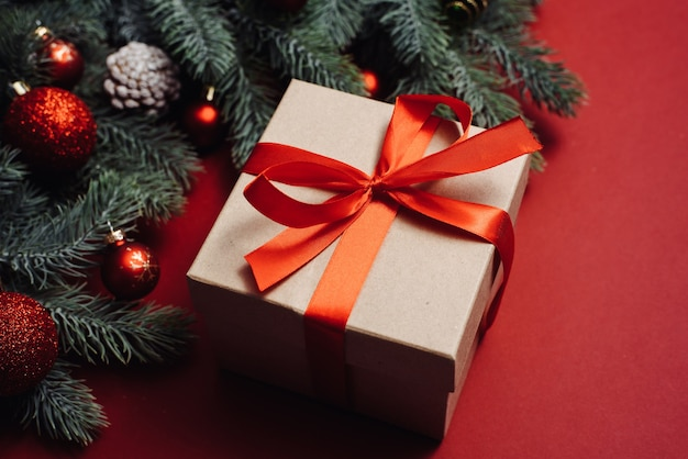 Basteln sie geschenk mit einem roten satinband neben weihnachtsbaumzweigen und -kugeln, spielzeug auf einem roten hintergrund.