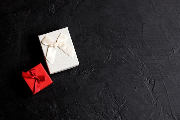 Basteln sie geschenkbox auf einem schwarzen hintergrund, verziert mit einer schleife. zum geburtstag, jubiläumsgeschenke, geschenkpostkarten.