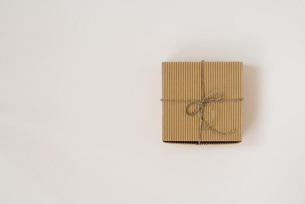 Basteln sie geschenkbox gebunden mit schnur mit auf beigem hintergrund. geburtstagsgeschenkverpackung. speicherplatz kopieren
