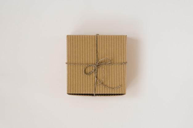 Basteln sie geschenkbox gebunden mit schnur mit auf beigem hintergrund. geburtstagsgeschenkverpackung.