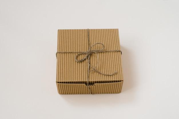 Basteln sie geschenkbox gebunden mit schnur mit auf beigem hintergrund. geschenkverpackung zum geburtstag im natürlichen stil