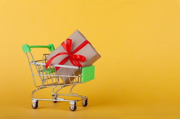 Basteln sie geschenkbox mit rotem band im einkaufswagen auf gelbem hintergrund,