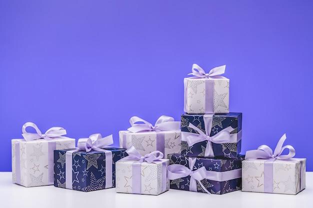 Basteln sie geschenke und blaues papier, verziert mit lila satinbandschleifen.
