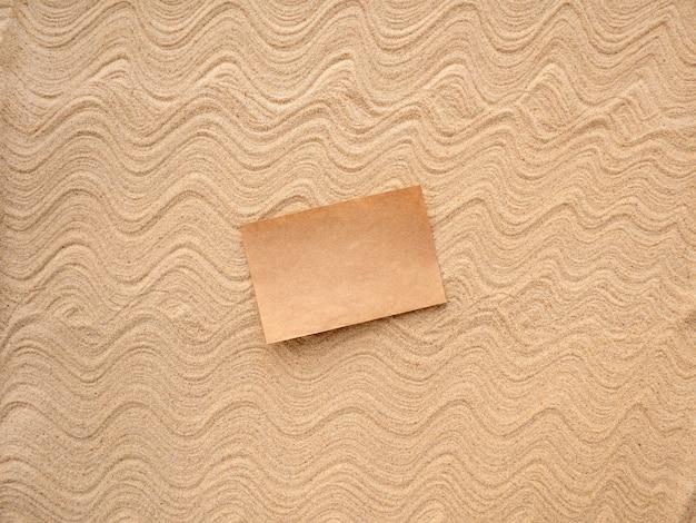 Bastelpapier zum schreiben auf gemustertem meersand.