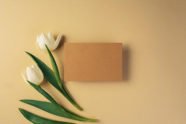 Bastelpapierkarte umgeben von frischen tulpen auf beiger oberfläche