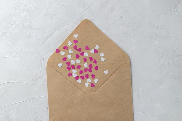 Bastelumschlag mit rosa und weißen papierherzen
