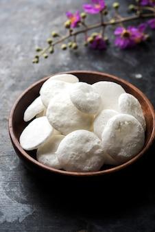 Batasha oder chilaka perlu wird aus zuckersiruptropfen hergestellt, es ist ein beliebtes essen der hinduistischen religion, das gott in tempeln angeboten wird. serviert in einem holzkorb oder einer schüssel. selektiver fokus