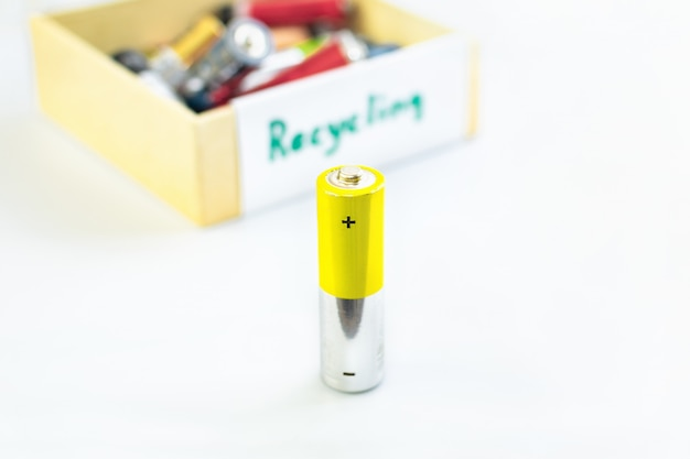 Batterie vor einer kiste mit gebrauchten batterien zum recycling