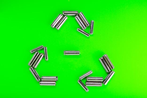 Batterien in form von recycling auf grün. batterie-recycling, umweltkonzept.