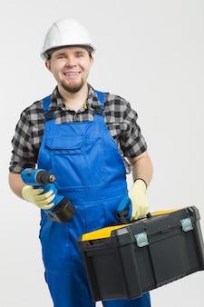 Bau-, bau- und arbeiterkonzept - hübscher baumeister mit werkzeugkasten und schraubendreher