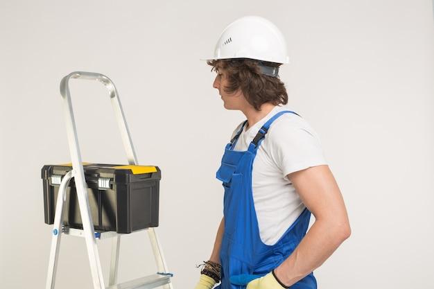 Bau-, bau- und arbeiterkonzept. lockiger baumeister mit werkzeugkasten und weißem helm