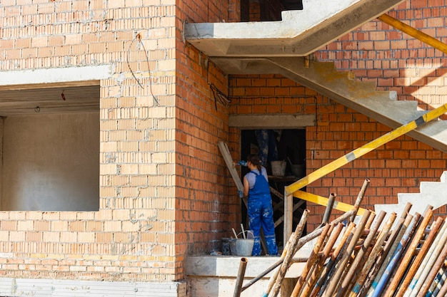 Bau eines mehrstöckigen gebäudes aus rotem backstein. arbeiterinnen verputzen ein backsteinhaus. industrie- und zivilbau. bausicherheit.