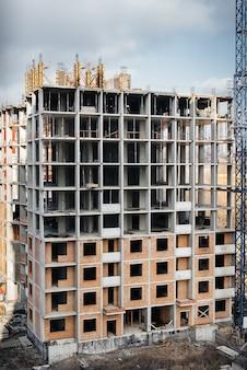 Bau eines modernen hochhaus-wolkenkratzers mit kränen im zentrum der metropole