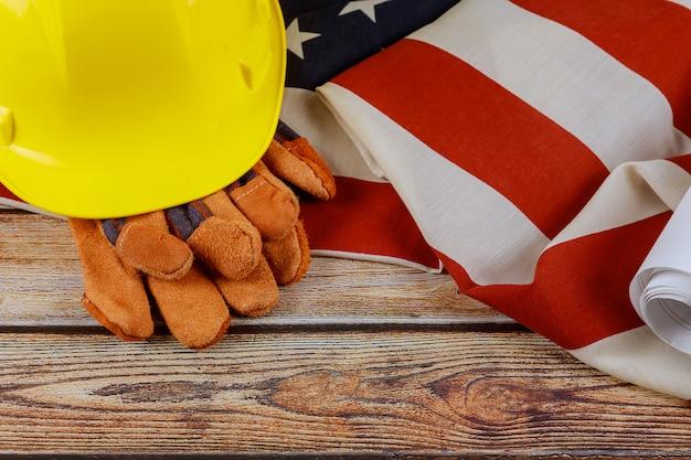 Bau gelber helm und lederhandschuhe am glücklichen tag der arbeit usa ein bundesfeiertag der vereinigten staaten amerika flagge patriotischen holz hintergrund