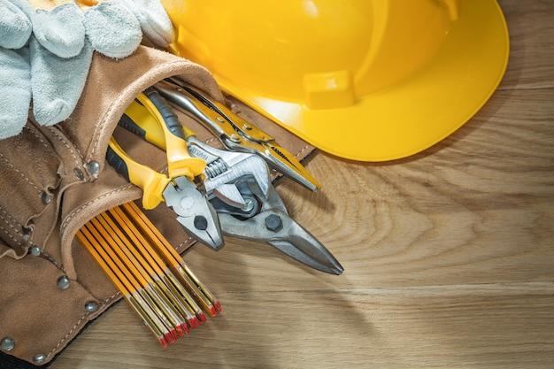 Bau helm sicherheitshandschuhe werkzeug gürtel werkzeug auf holzbrett
