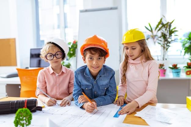 Bau in der schule. drei süße kinder fühlen sich gut beim bauen in der schule, während sie skizzen machen sketch