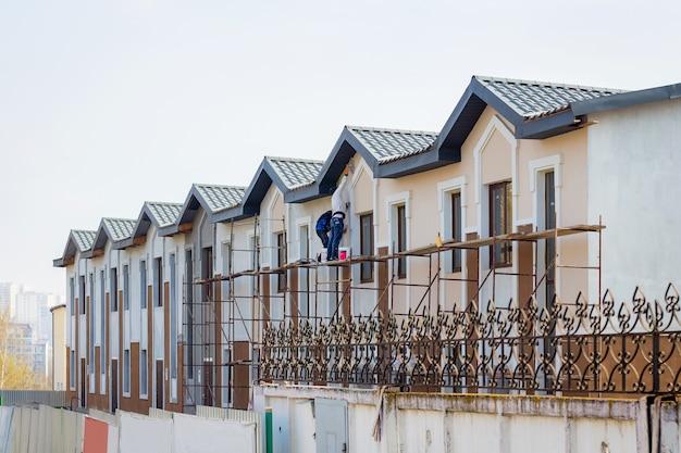 Bau moderner gebäude. meister arbeiten an der fertigstellung des hauses