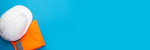 Bau-schutzhelm mit sicherheitsweste lokalisiert auf blau