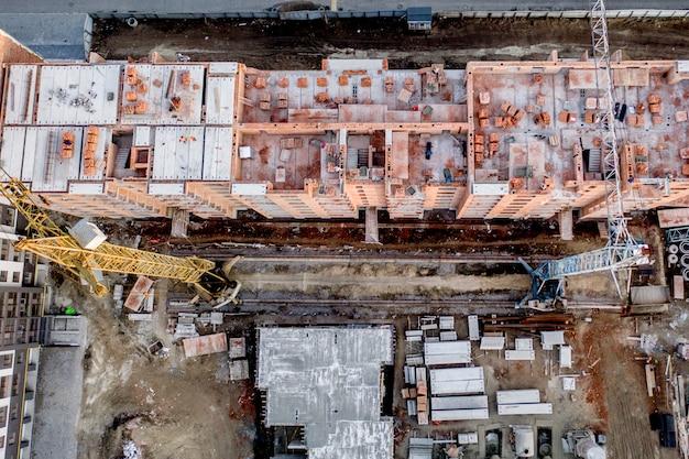 Bau und bau von hochhäusern, der bauindustrie mit arbeitsmitteln und arbeitern. blick von oben, von oben. hintergrund und textur