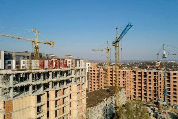 Bau und bau von hochhäusern, die bauindustrie mit arbeitsgeräten und arbeitern. ansicht von oben, von oben.