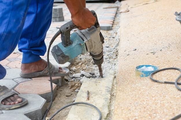 Bauarbeit, die zementbeton auf fußweg unter verwendung der elektrischen mörserbohrmaschine bohrt. bau arbeitskonzept.