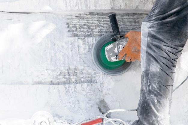 Bauarbeiten des weißen steinausschnitts durch trennsäge mit diamantscheibe