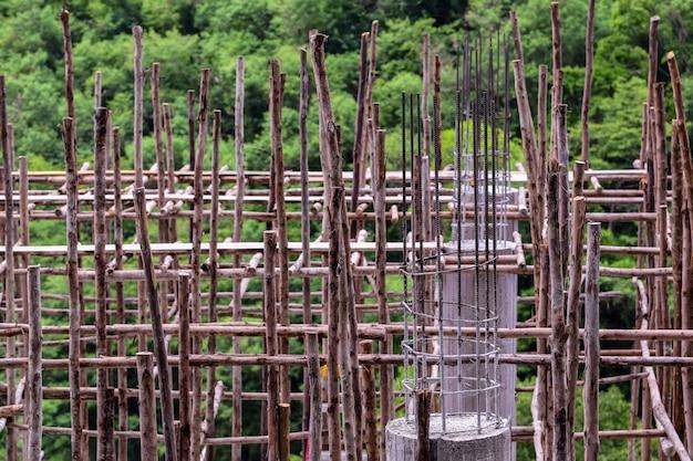 Bauarbeiten mit zement und holz, gießen von betonmörtelsäulen, gerüste und bauarbeiten, gebäude im wald