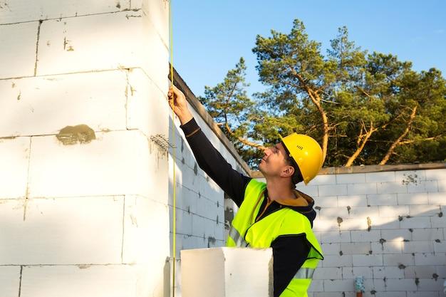 Bauarbeiter auf der baustelle misst die länge der fensteröffnung und der wand mit maßband. cottage besteht aus porösen betonblöcken, schutzkleidung - schutzhelm und weste