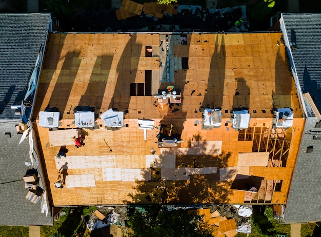 Bauarbeiter auf einem ersatzschindeldach installierte das haus neue schindeln