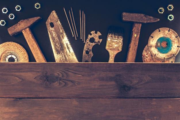 Bauarbeiter bearbeitet erbauerhammer, säge, nägel, schraubendreher auf einem hölzernen hintergrund