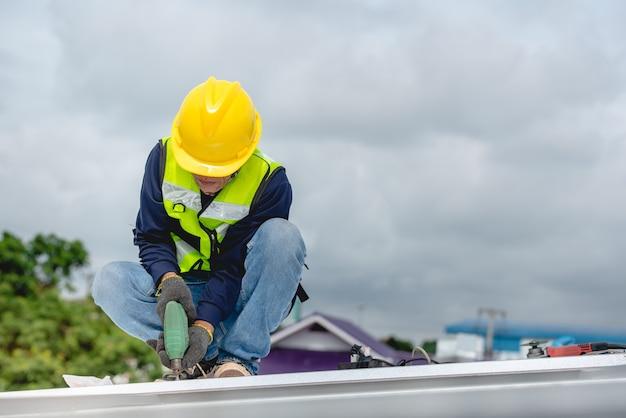 Bauarbeiter befinden sich auf der stahldachkonstruktion des gebäudes im baubereich. ziehen sie die mutter mit einer elektrischen bohrmaschine fest oder installieren sie das dach des hauses.