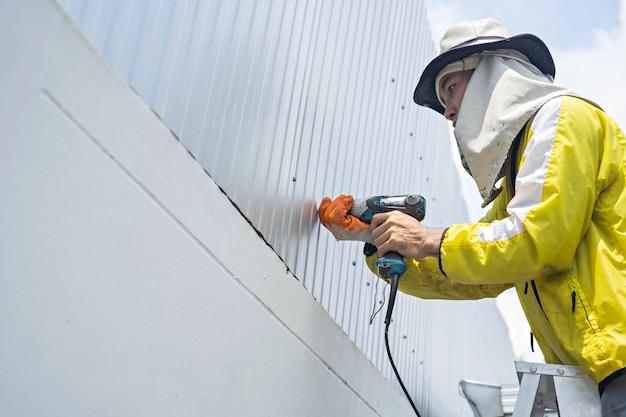 Bauarbeiter benutzt elektroschrauber und reparieren des metallwandrahmens.