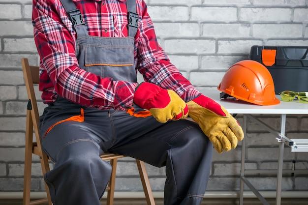 Bauarbeiter, der am arbeitsplatz schutzhandschuhe anzieht.